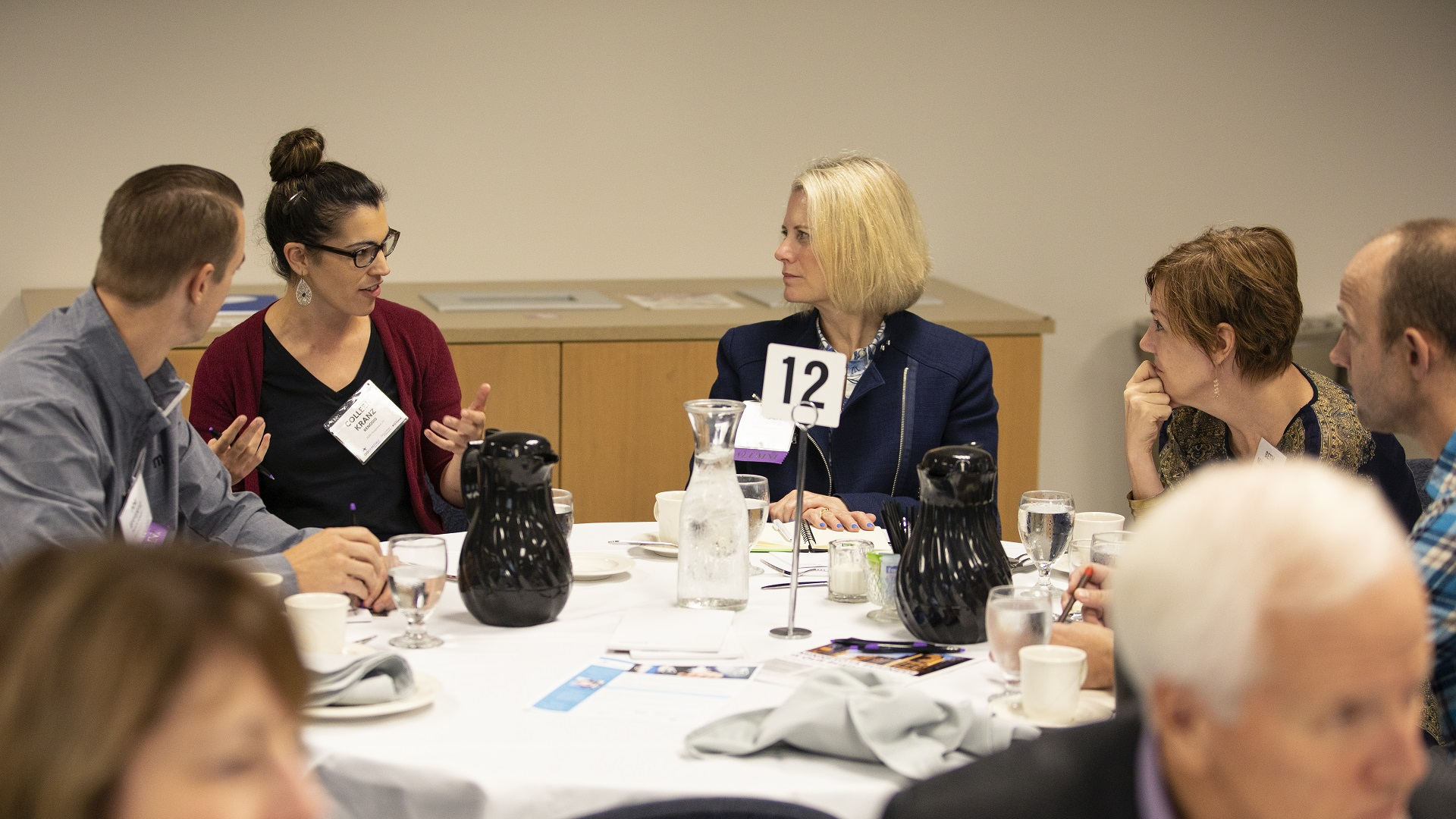 Event participants discuss a topic amongst themselves at a table