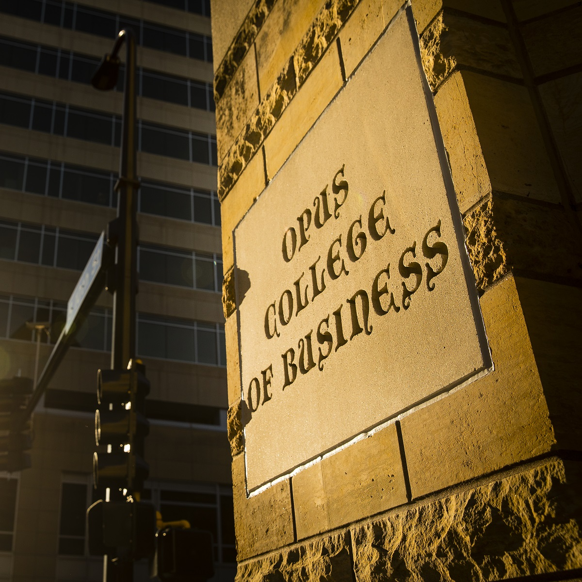 A closeup of the Opus College of Business name on the exterior of a building on the downtown Minneapolis campus.