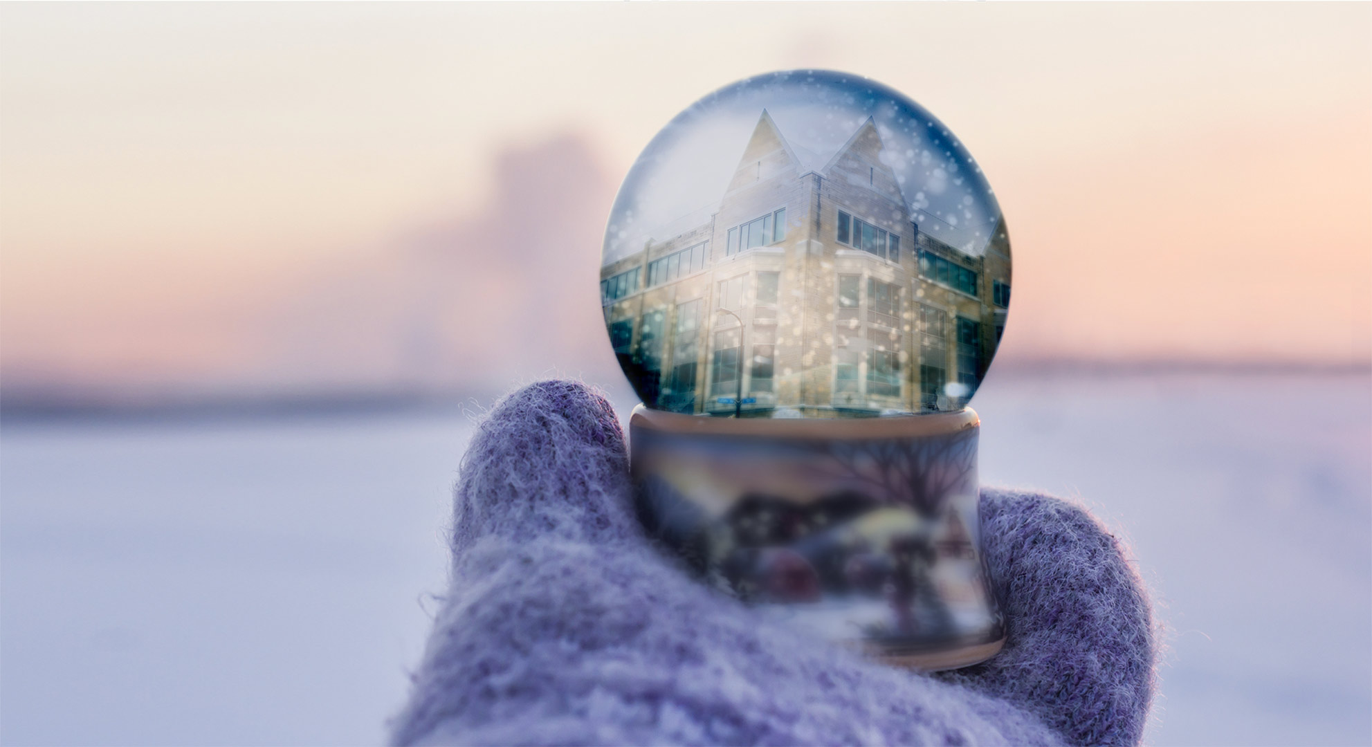 A person holding a snow globe with a reflection of Opus College of Business