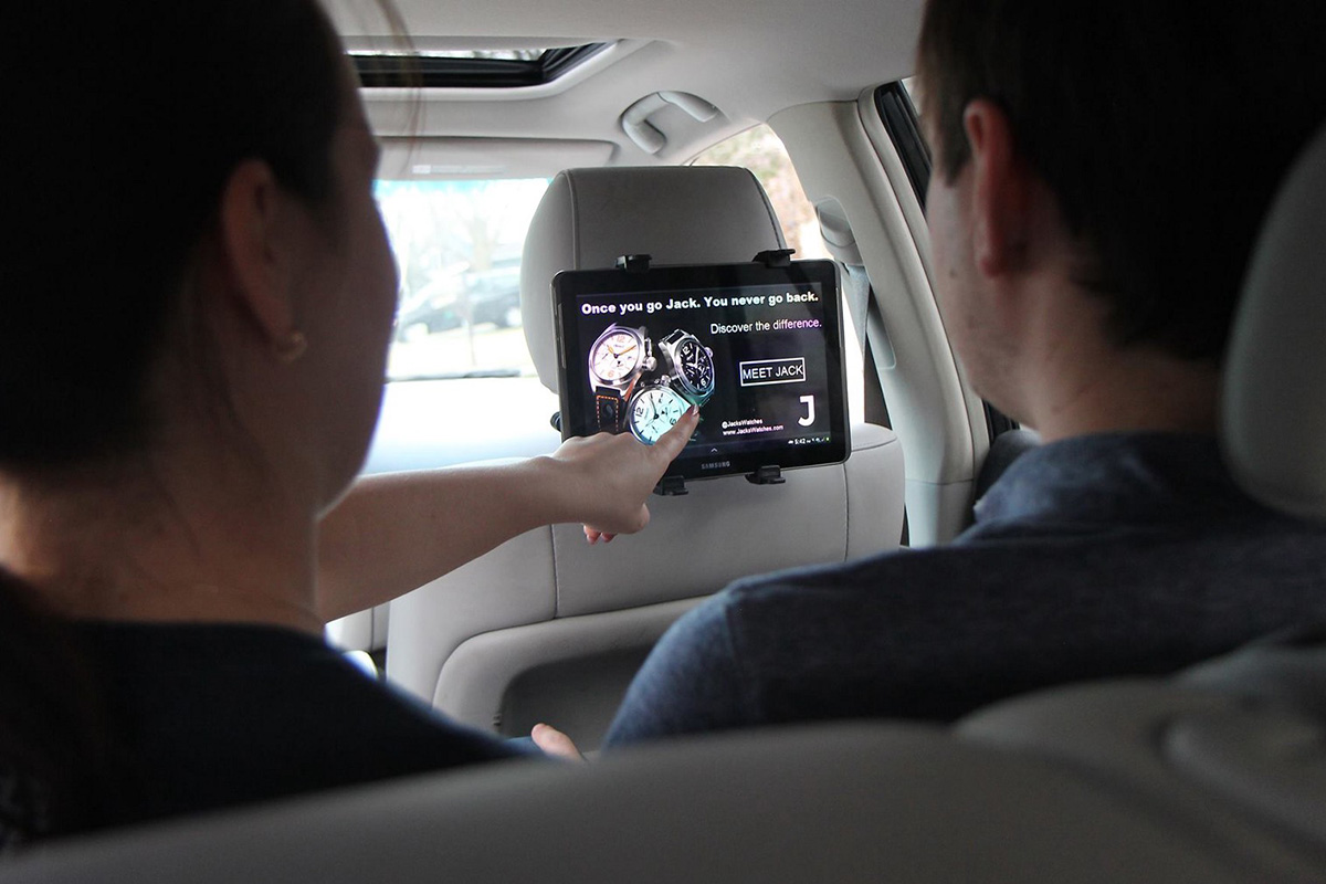Two people in a car, pointing to and using the Vugo device.