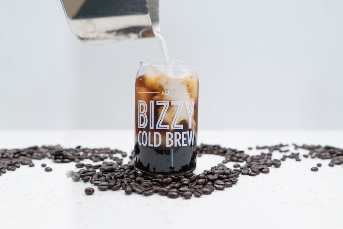 Milk is poured into a cup of Bizzy's Cold Brew.