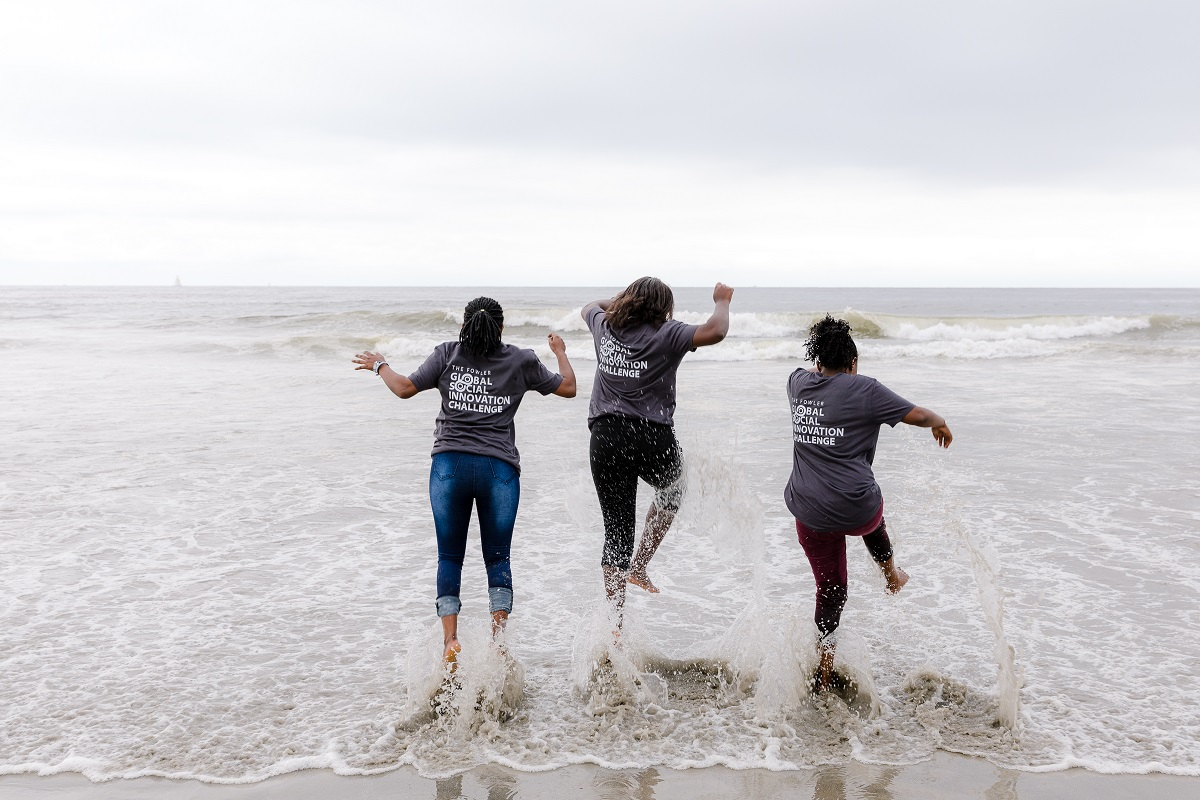 Three women wearing Fowler Global Social Innovation Challenge t-shirts splash in the ocean.