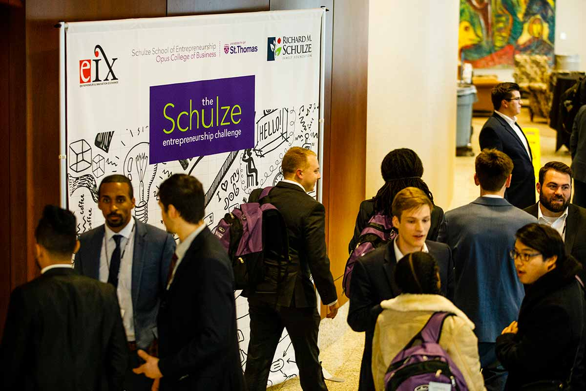 Guests walk past a Schulze Entrepreneurship Challenge sign during the e-Fest Schulze Entrepreneurship Challenge April 14, 2018 in Schulze Hall auditorium.