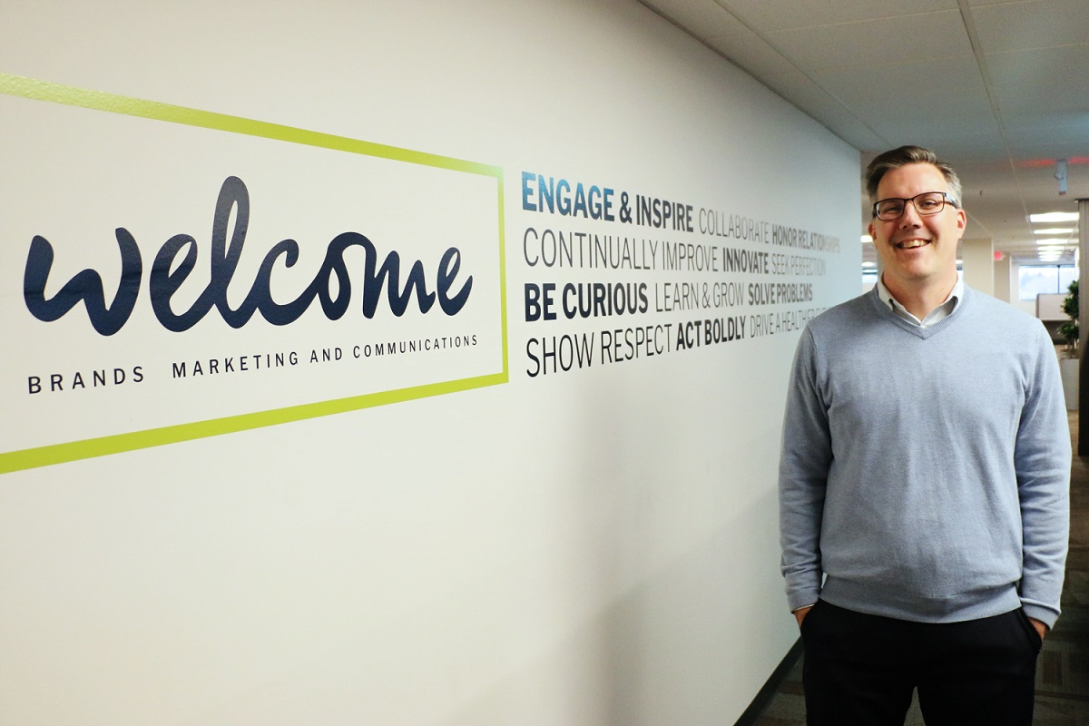 Jeremy Kennedy in front of welcome wall graphic.