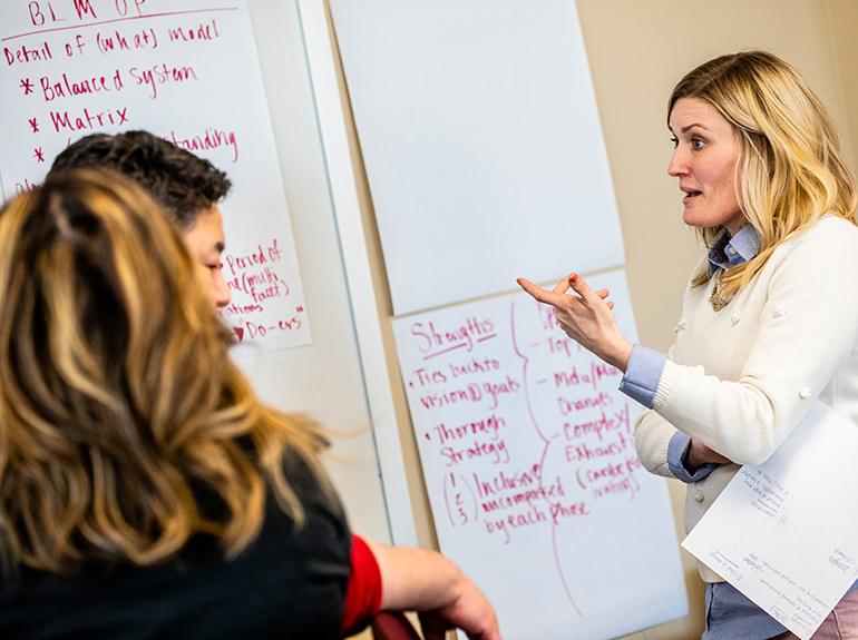 A female student participates in a group exercise during an Opus College of Business class.