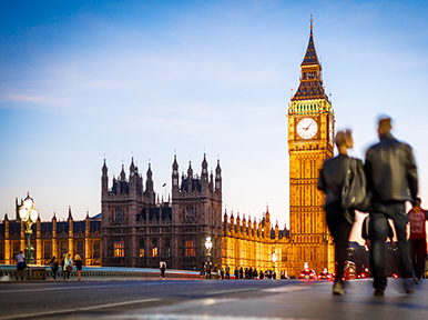 People walking on Westminster Bridge in London, England with Big Ben and the House of Parliament in the background.