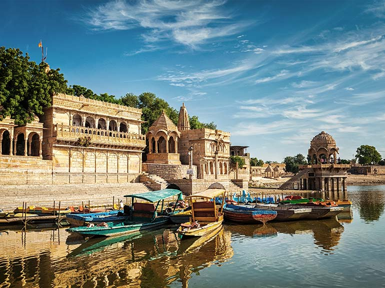 Small wooden boats docked in front of a temple in Jaisalmer, India.