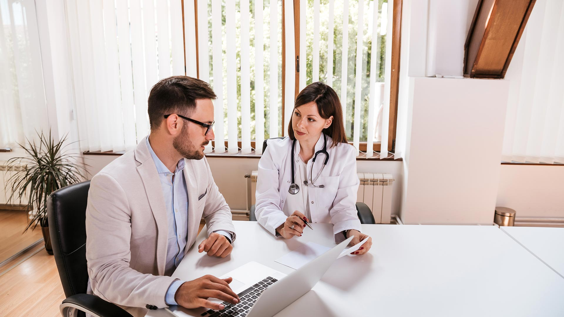 Health care business professional speaks with a medical doctor in an office.
