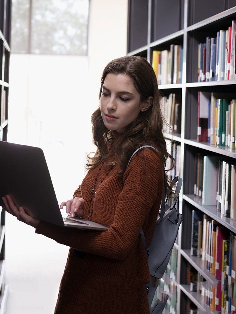 A student standing between bookshelves using a laptop in the library.