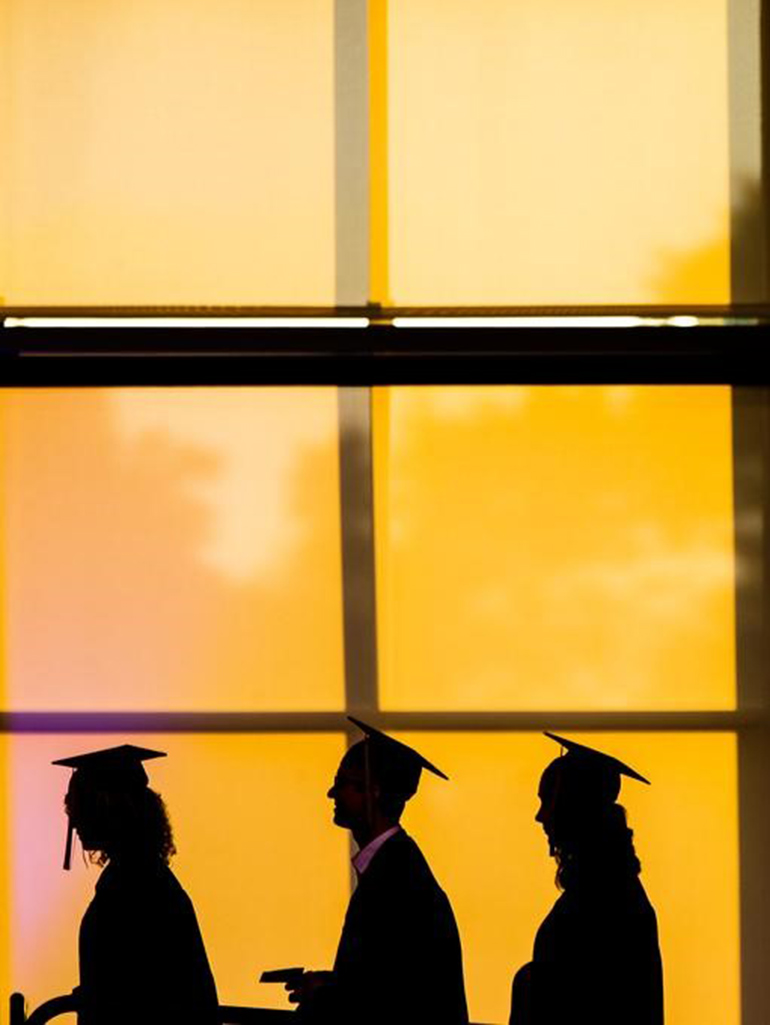 Students walking in cap and gown at a commencement ceremony.