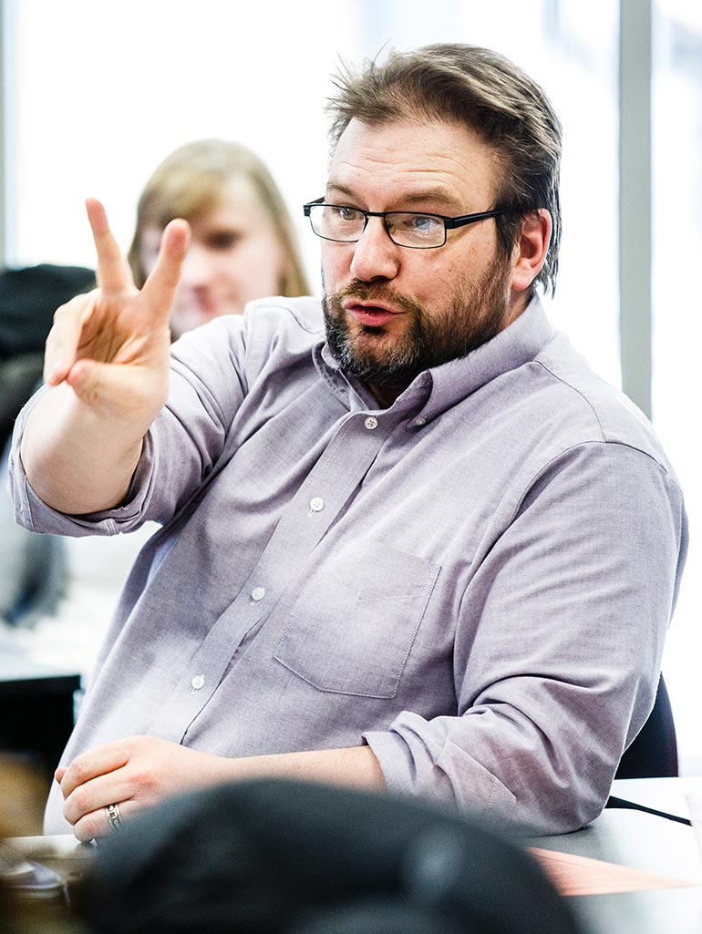 "A student makes the hand signal for ""two"" while participating in a class discussion in the Opus College of Business in Terrence Murphy Hall."