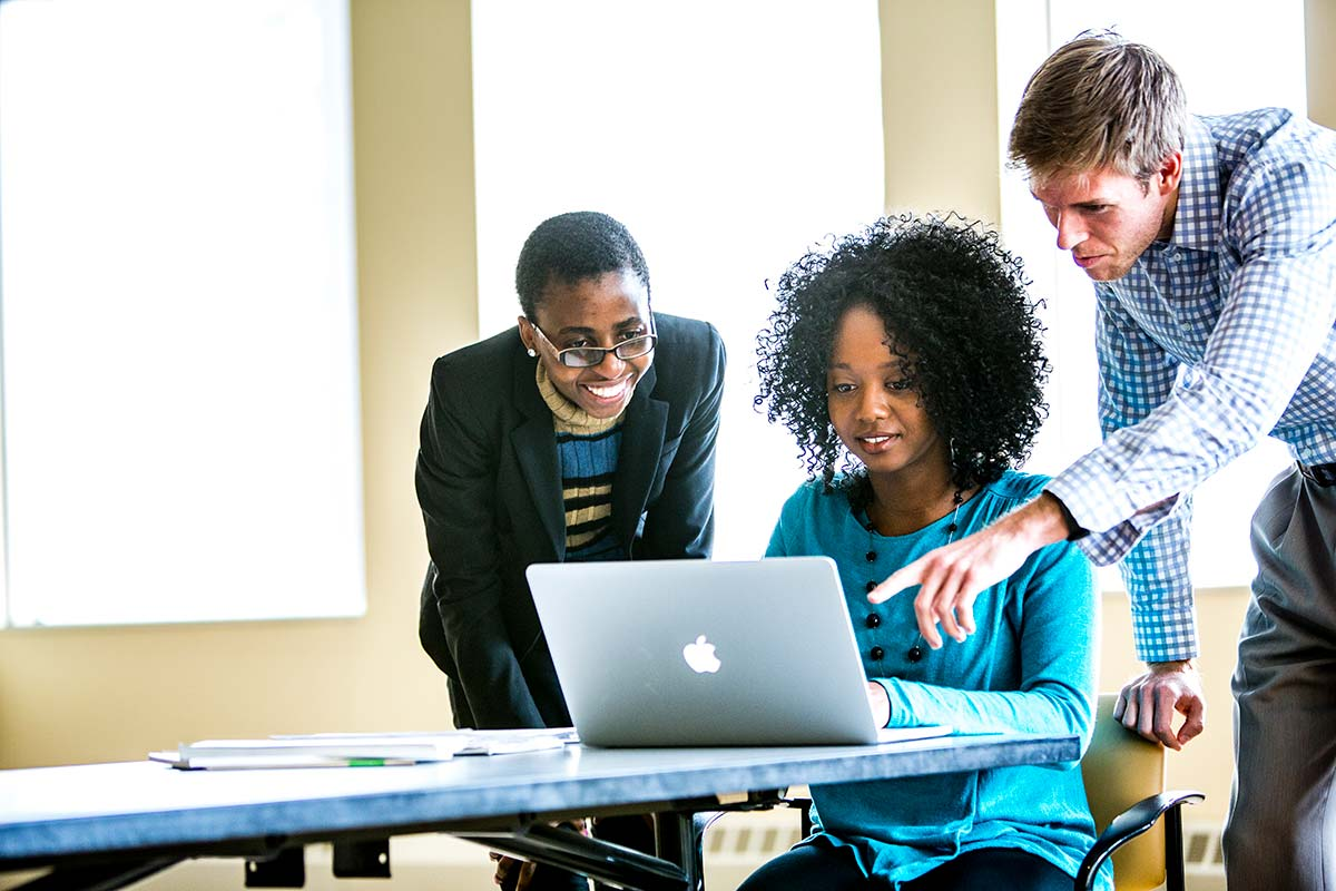 Three MBA students work around a computer in Schulze Hall in Minneapolis, two stand and look over the shoulder of the third student.