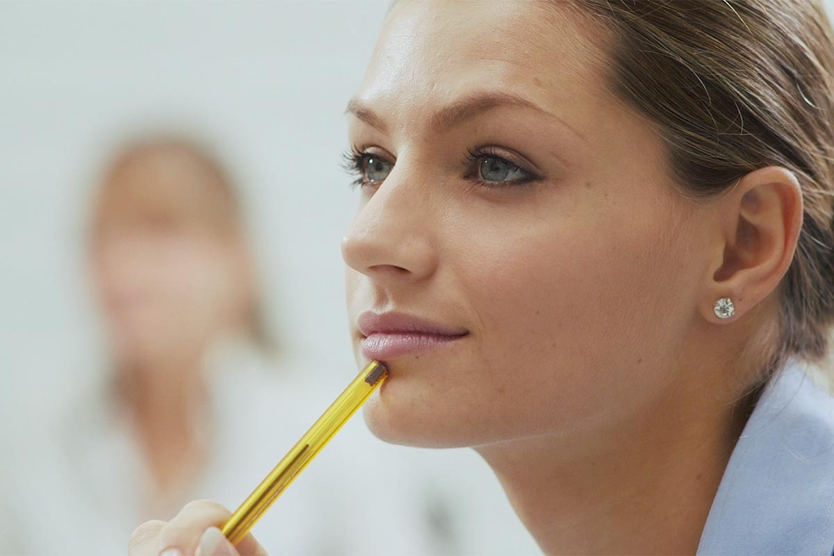 Closeup on a woman looking focused and holding the end of her pen against her chin.