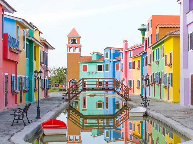 Colorful buildings around a bridge and canal in a international town.