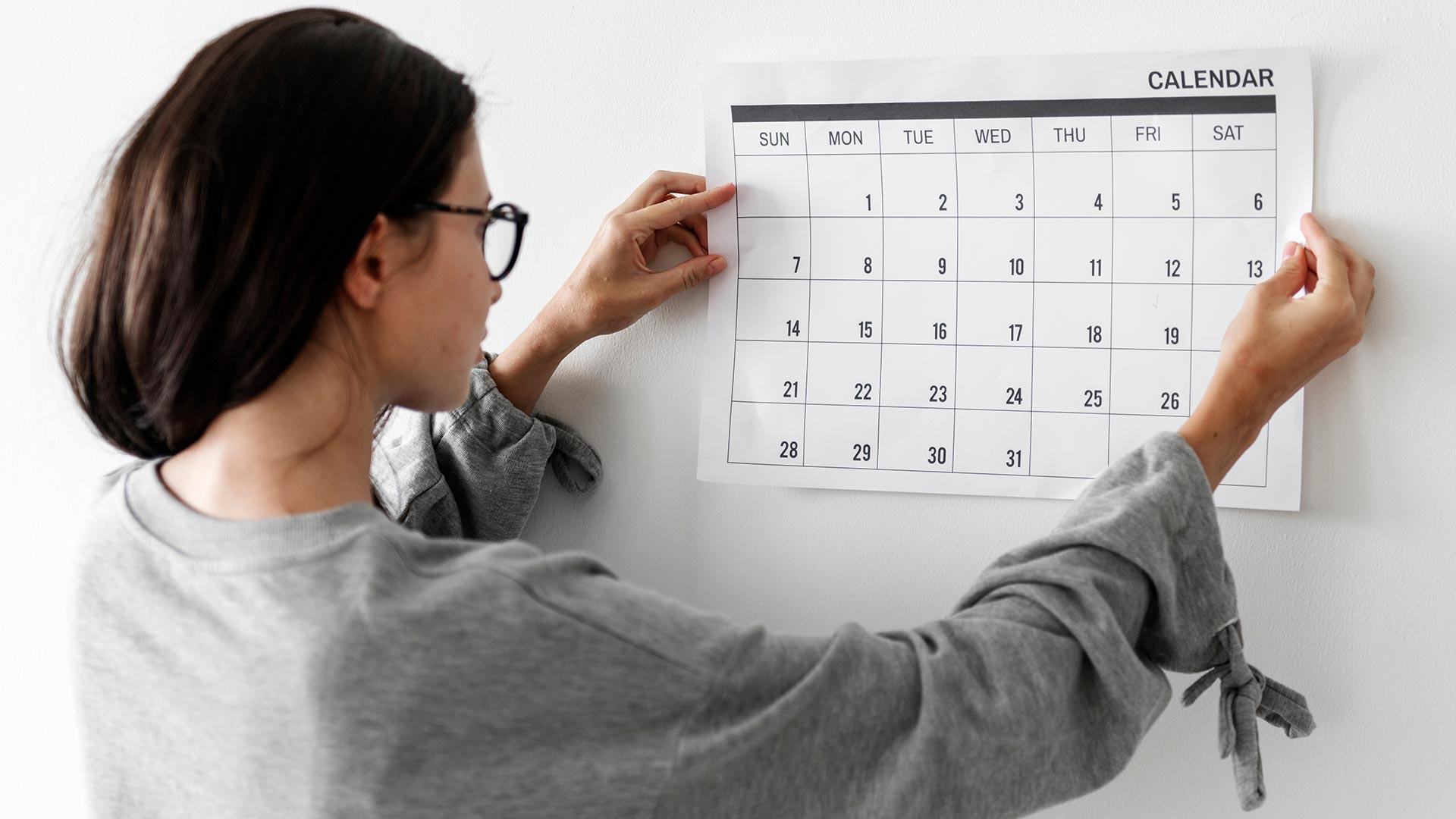 Student holding a paper monthly calendar up to a wall.
