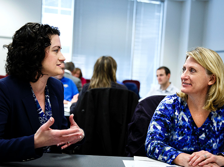Professor Stacey Larson (left) works with student.