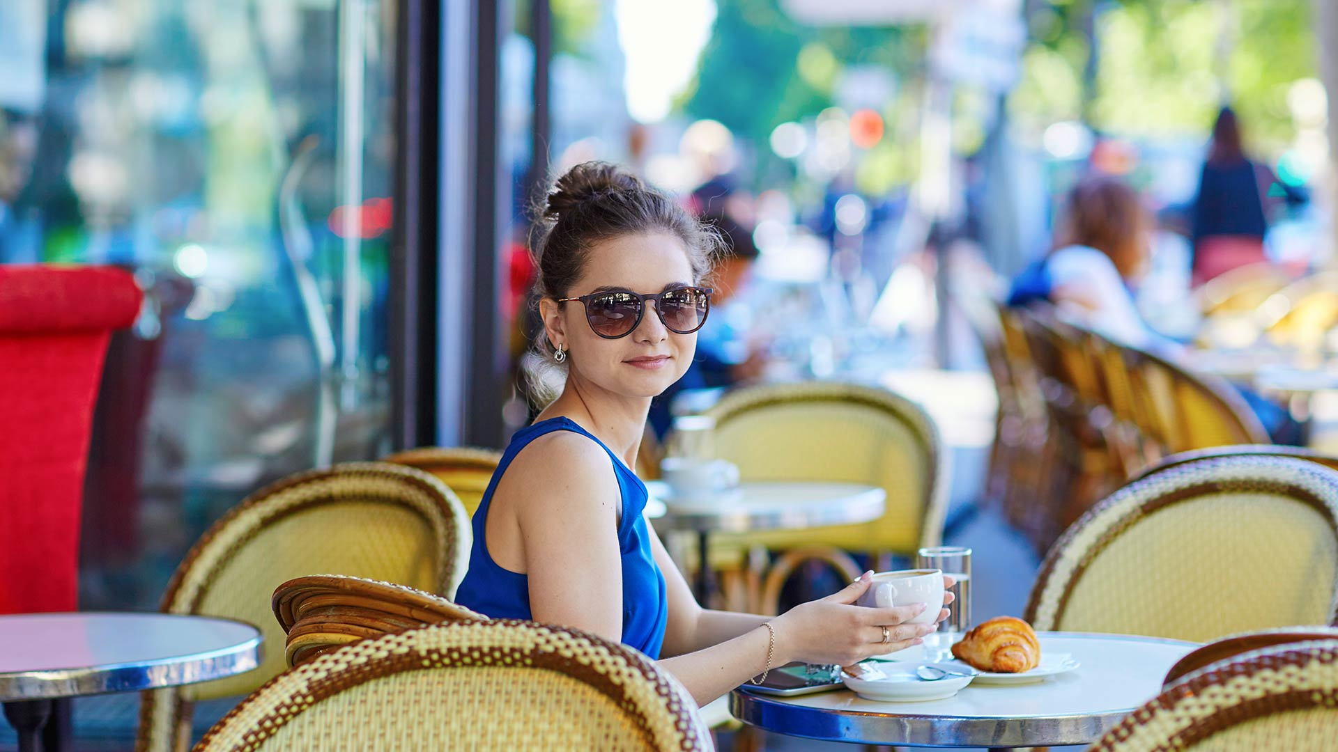 Woman wearing sunglasses, sitting in a cafe in an international location with coffee and a croissant.