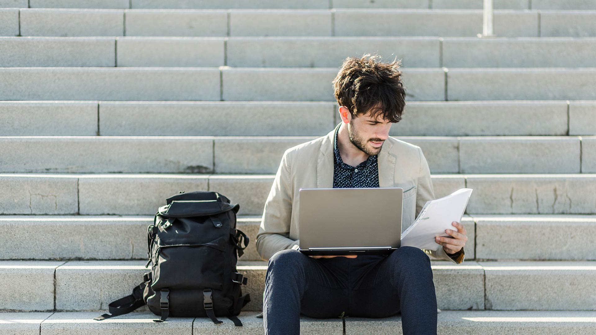 Man studying on outdoor stairs with a laptop and his backpack beside him.