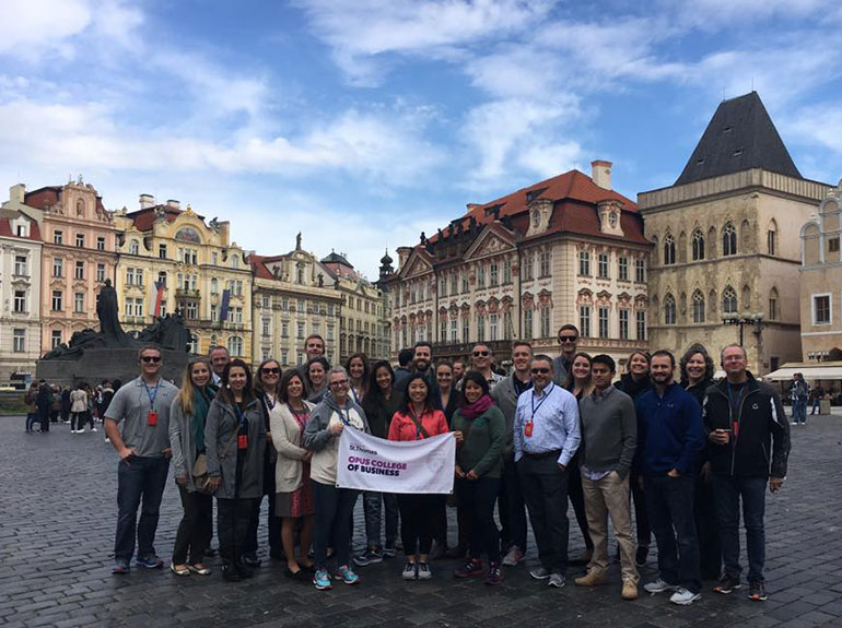 "Group of students stand outside in a city square hold a banner saying ""Opus College of Business"" during a study abroad trip in Eastern Europe."