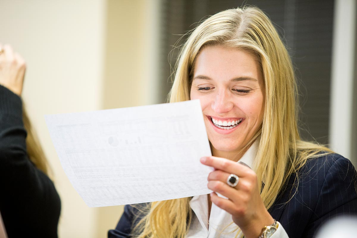 A woman is smiling and reviewing some paperwork.