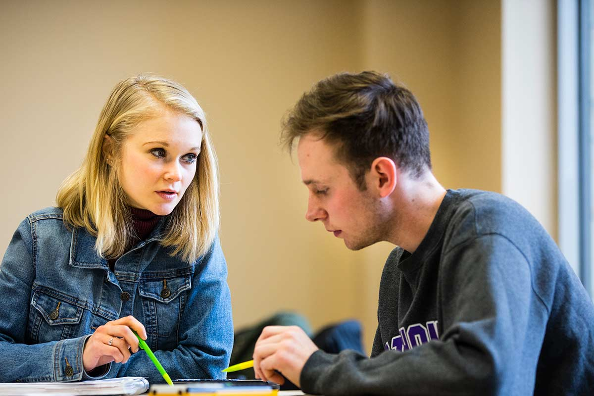 Megan Huggett, left, and Adrian Trow talk over papers during a staged photoshoot with Opus College of Business student tutors in McNeely Hall on March 20, 2018 in St. Paul.