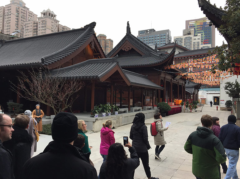 A group of tourists walks by and snaps photos of the Yufo Temple in Shanghai.