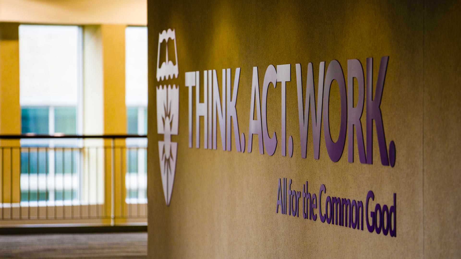 "A sign reading ""Think. Act. Work. All for the Common Good"" is shown in the skyway."