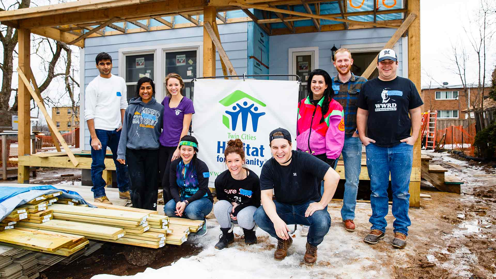 Students pose outside a Habitat for Humanity home during a service project.