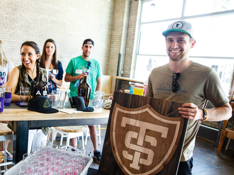 Alum Garrett Faust, '13, owner of Uptown Woodworks, holds a St. Thomas shield sign made by his business during a Young Alumni Council social event.