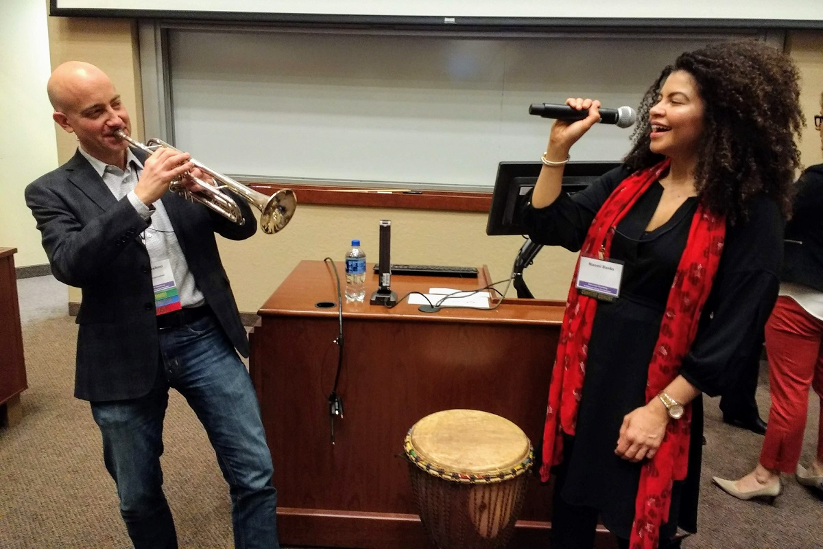 A man plays a horn instrument while a woman sings into a microphone at the 2019 Executive Coaching in Organizations Conference. Photo by Brant Skogrand.