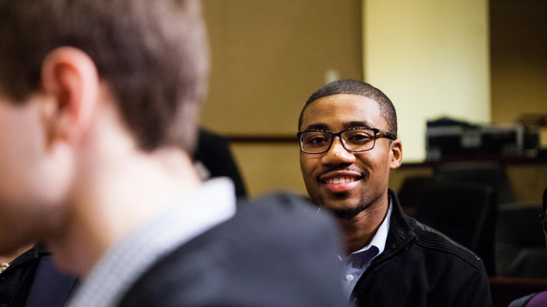 A guest waits in line to speak to someone at an Opus College of Business event.