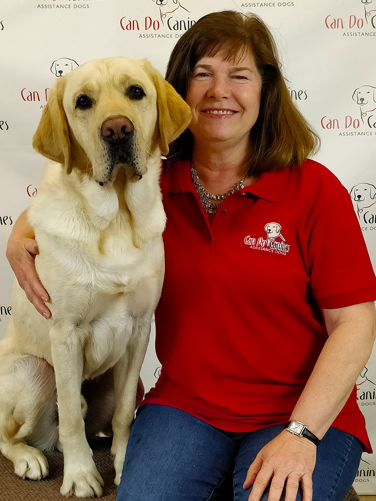Debra Ouellette sits with her arm around a yellow lab service dog in front of a Can Do Canines wall graphic.