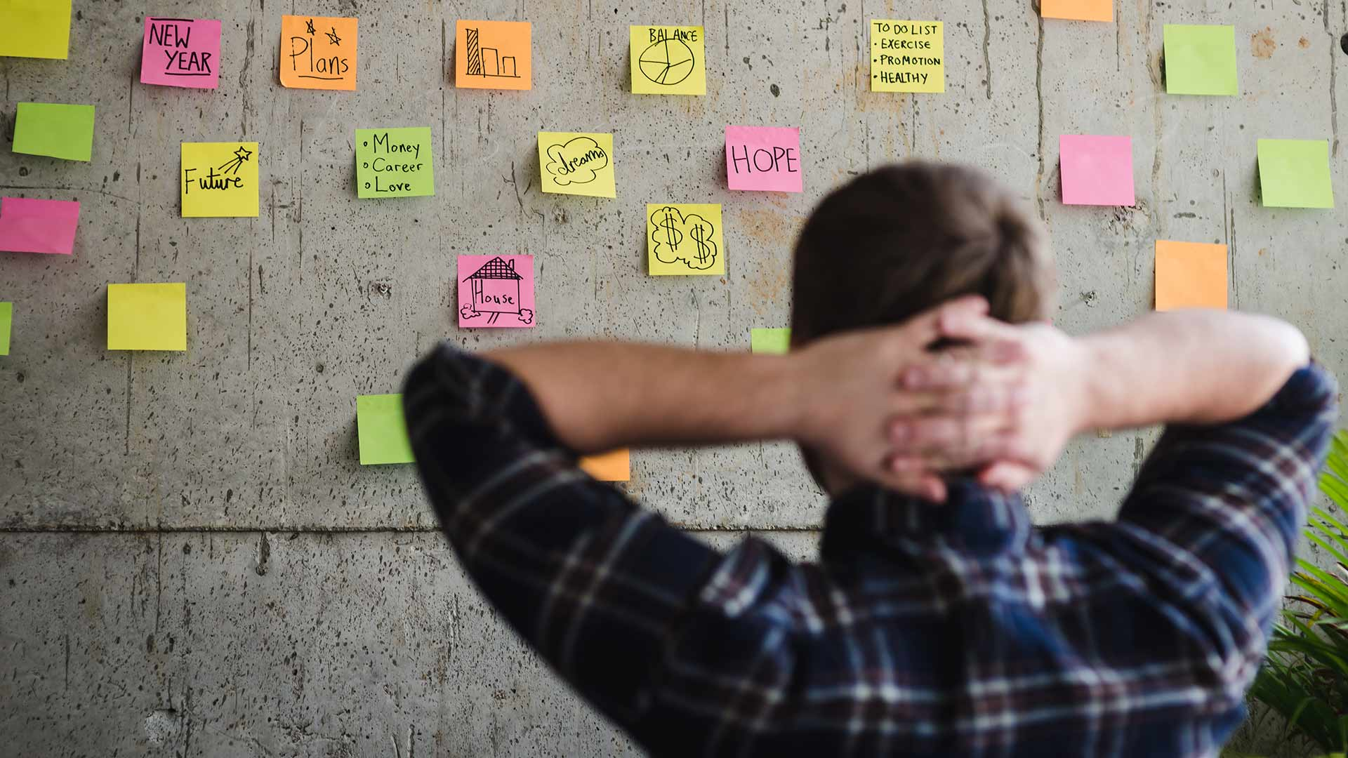 Man looking at a wall covered in post-it notes.