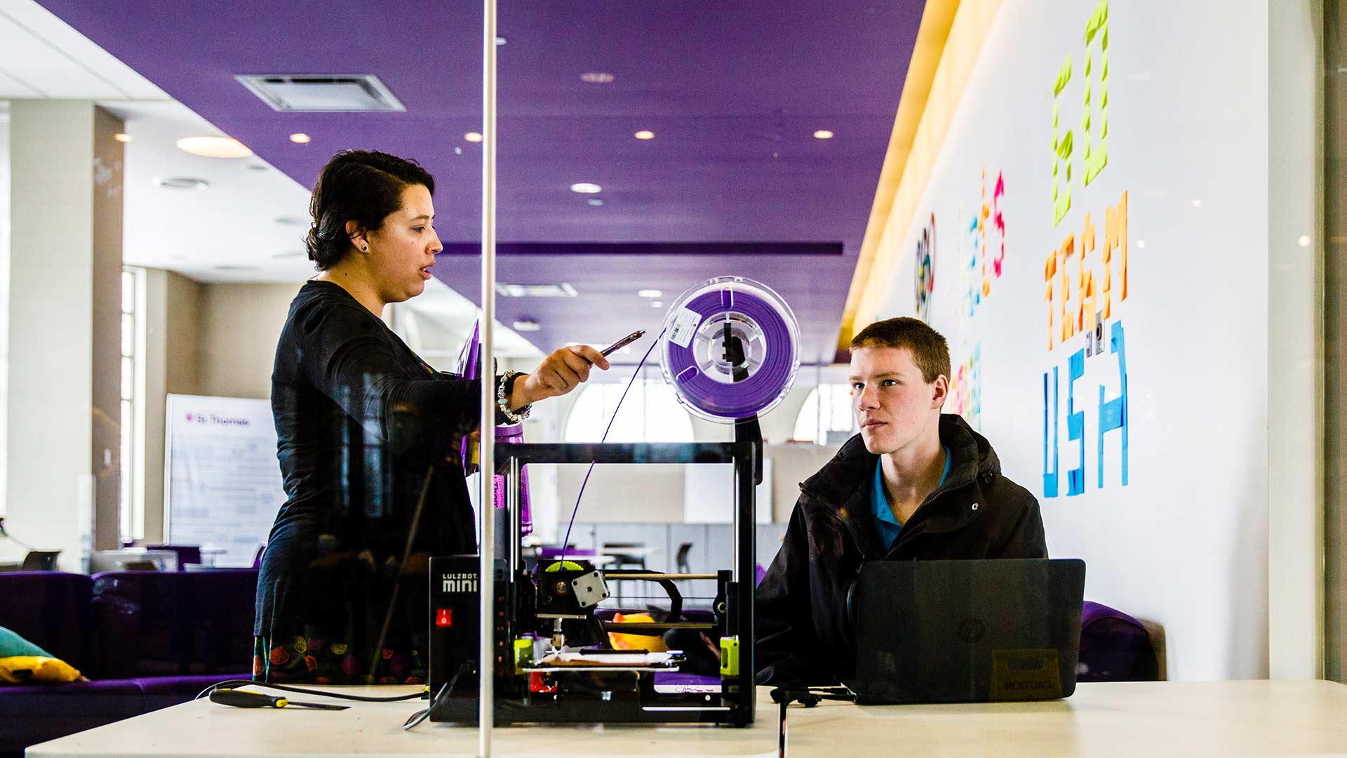 Two people work with a 3D printer in the create space.