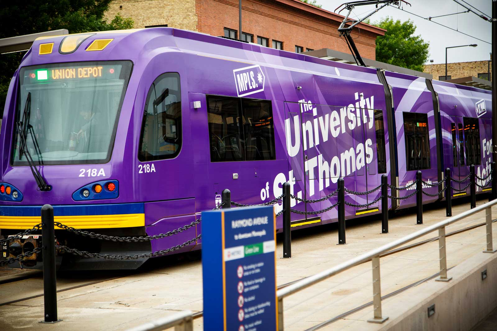 Minneapolis Lightrail with purple St. Thomas wrap comes into a station.