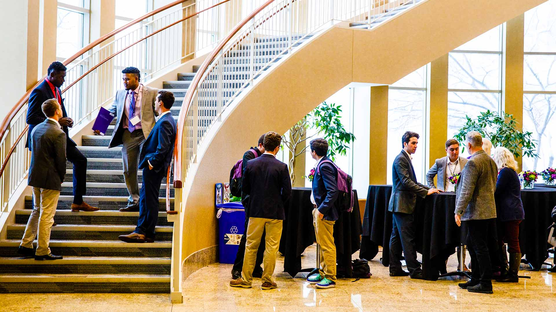 Guests converse during an event held in the Schulze Hall atrium.