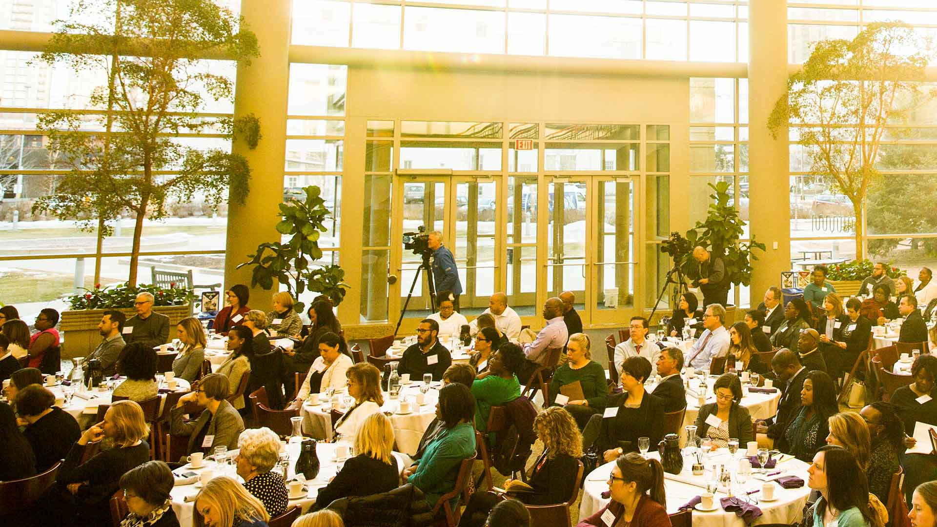 Attendees listen to a speech over dinner at the Schulze Atrium.