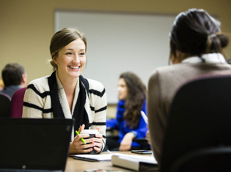 Lady sitting and smiling while talking to a colleague.