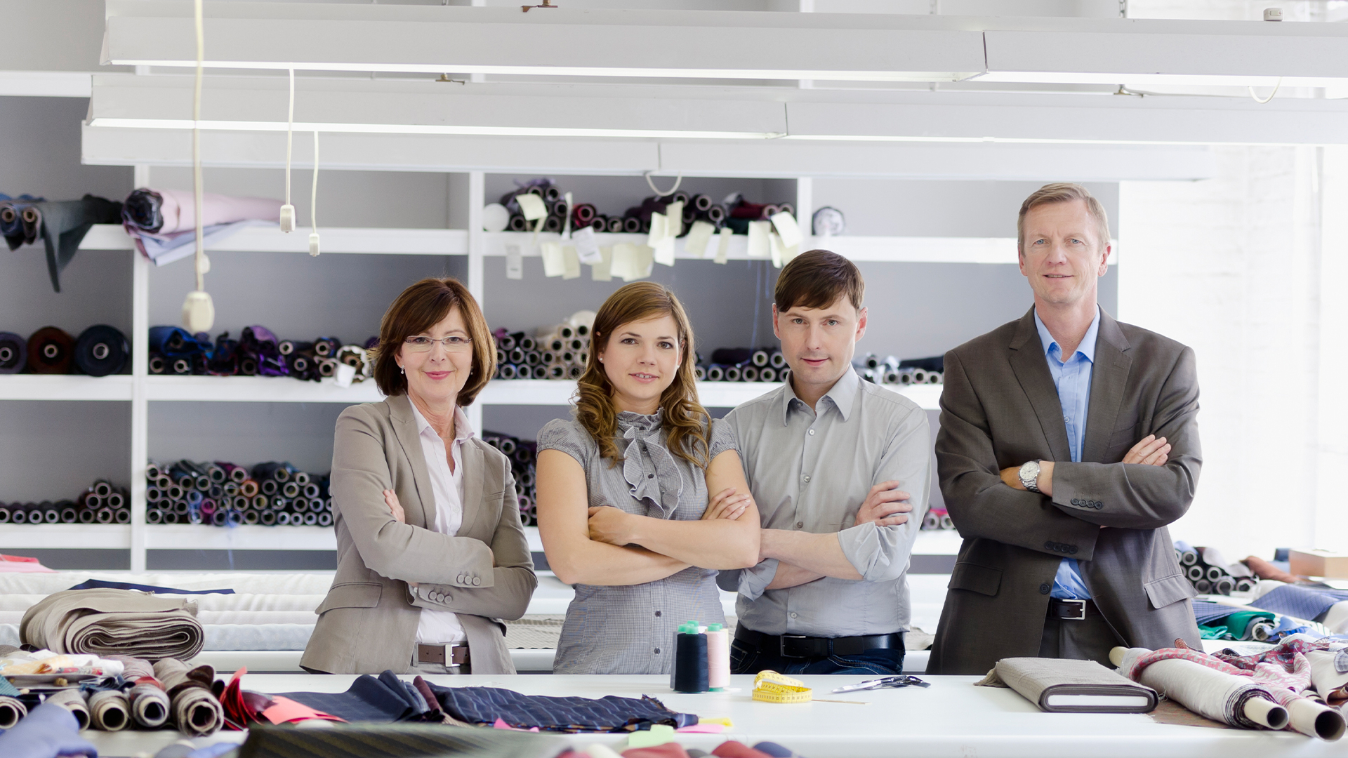 Four individuals stand in a textile workshop with their arms crossed.