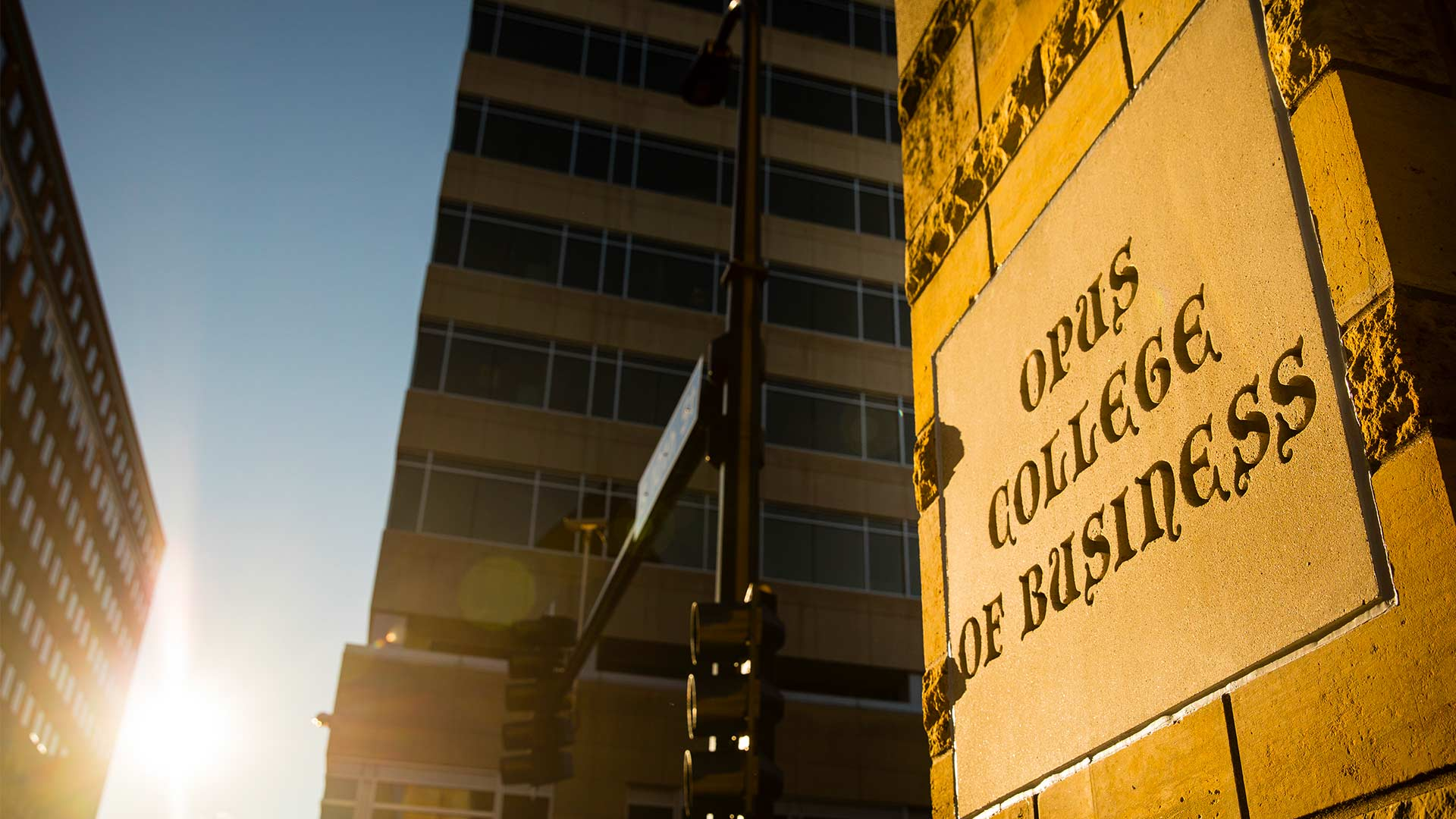 The sun shines on a sign for Opus College of Business.