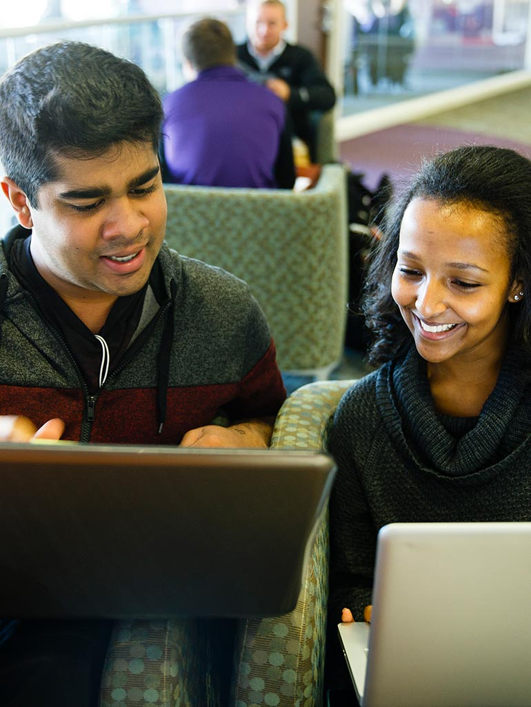 Two students smile as they work on their laptops while sitting on a couch.